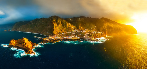 Aerial view of Porto Moniz at sunset with warm sun light and storm clouds gathering