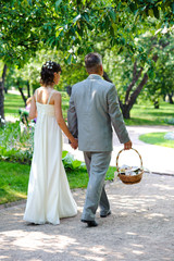 The bride and groom young couple walking in the park. Wedding day in summer.