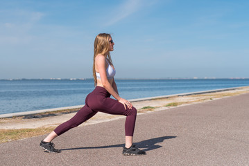 Fitness Model in Sportswear Outdoors near the Beach Stretching