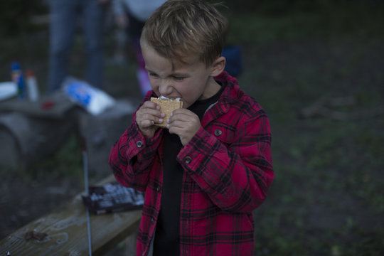 A little boy eating a s'more while standing outdoors