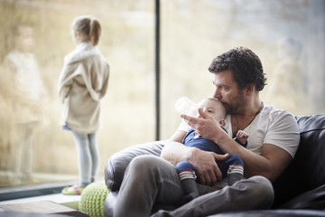 Father bottle feeding baby on couch with daughter at the window