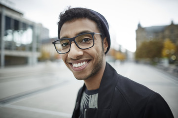 Portrait of smiling young man with glasses outdoors