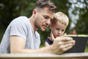 Father and son looking at digital tablet