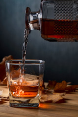 Whiskey is poured into a glass from a carafe.