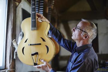 Guitar maker examining electric guitar in his workshop