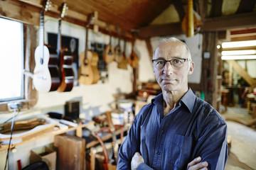 Portrait of a confident guitar maker in his workshop