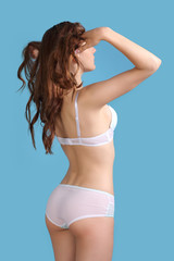 girl posing in sexy underwear on a blue background