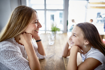 Happy mother and daughter sitting face to face in a restaurant