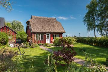 Schöner Garten eines typischen Dorfhaus mit Reetdach an der Ostsee