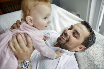 Father holding his baby girl while lying on bed