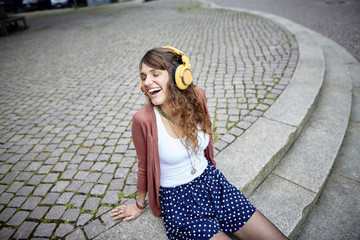 Happy young woman sitting on a square listening to music