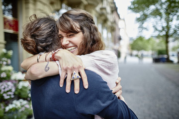 Smiling young couple hugging on road in city