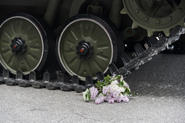 A bouquet of lilac on the road under the wheels of the tank.