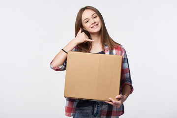 Delivery, relocation and unpacking. Smiling young woman holding cardboard box showing call me gesture. Call center and customer support service concept.