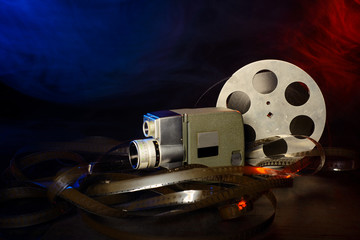 8 mm movie camera with a reel of film in blue and red smoke