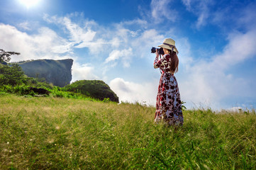 Wall Mural - Woman standing on meadow and holding camera take photo at Phu Chi Fa mountains in Chiangrai, Thailand. Travel concept.
