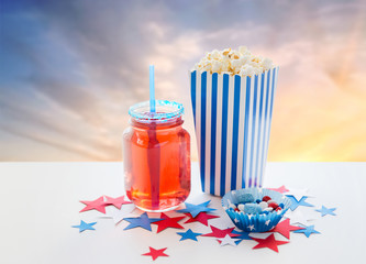 american independence day, celebration, patriotism and holidays concept - close up of berry lemonade drink in glass or mason jar, popcorn and candies with stars confetti decoration at 4th july party