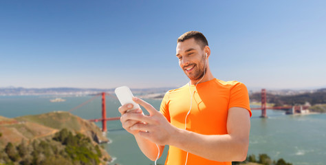 fitness, sport and technology concept - smiling man with smartphone and earphones listening to music over golden gate bridge in san francisco bay background