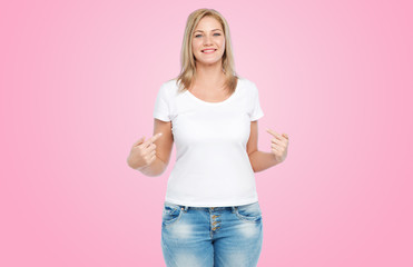 body positive, plus size and people concept - happy woman in white t-shirt pointing fingers to herself over pink background