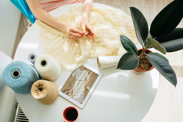 Top view of craftswoman's hands knitting something with crochet in cozy workplace at home interior. Female working with tender lace. Business handmade crochet relaxation concept.