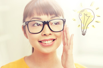 people, education, vision and portrait concept - happy asian young woman or teenage student girl in glasses over light bulb doodle
