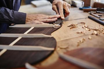 Close-up of a guitar maker at work
