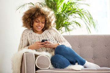 young african woman relaxing at home and using mobile phone