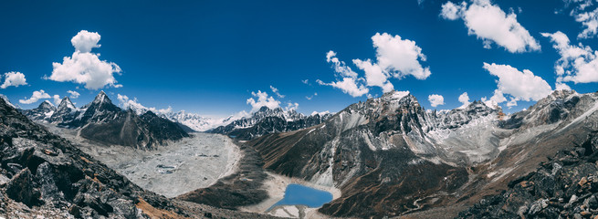 Wall Mural - Amazing panoramic view the mighty Himalayas and peaceful Gokyo Lake on the blue cloudy sky background. Everest Base Camp trek in the Sagarmatha National Park in the north-eastern Nepal.