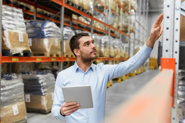 logistic business, technology and shipment concept - businessman with tablet pc computer checking goods at warehouse