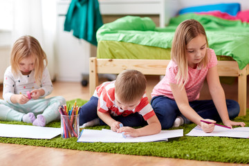 childhood, leisure and people concept - happy kids drawing and making crafts at home