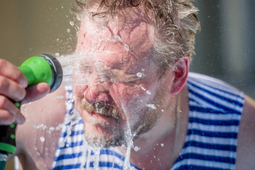 The man pours on the person water from a hose