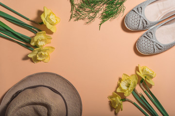 Travel background concept. The view from the top. Sports light Slippers, hat, flowers-daffodils. Color peach background. The view from the top. Label space.