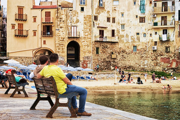 Seaside with people sitting on benches at Cefalu Sicily