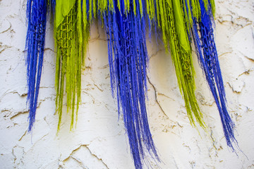 Purple and lime green fringed scarves blow against a rough stucco wall - boho background