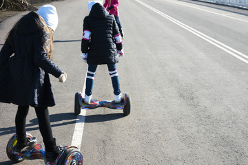 Two girls ride a two-wheeled Hoverboard. Happy childhood concept. Copy space.