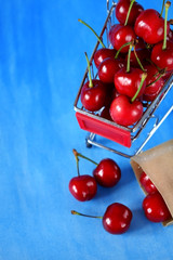 Cherries in a shopping trolley against blue background. Copy space