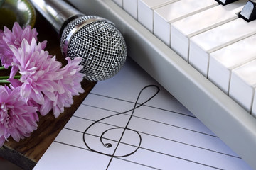 Treble clef and musical staff on white paper. Synthesizer, microphone and flowers around