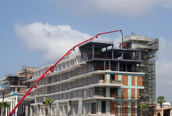 construction site with a large red telescopic crane and building workers building a large modern hotel complex in cyprus