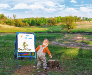 Little boy is drawing on a canvas of paper on an easel against the background of picturesque nature. Young artist painter with brush and palette of colors.