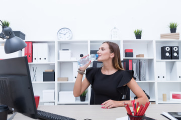 Beautiful girl drinking water from a bottle in the office