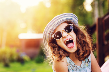 summer portrait of happy kid girl on vacation in sunglasses and hat, laugh and showing tongue.