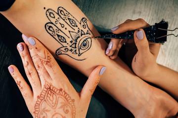 Artist applying henna mehndi tattoo on female hand