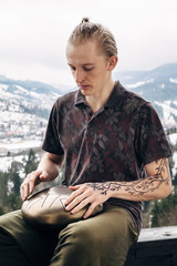 Young blond hipster playing hang drum with fingers