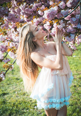 Woman smelling delicate aroma of blooming tree. Tourist from Europe in love with Japan enjoying sakura season. Female traveler exploring culture of land of rising sun, wanderlust concept