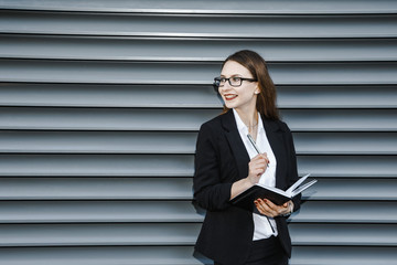 A young woman in a business suit is near the office. Business woman in glasses and a notebook. The girl is making notes on her daily party. Good girl smiles. The lady stands near a gray wall.