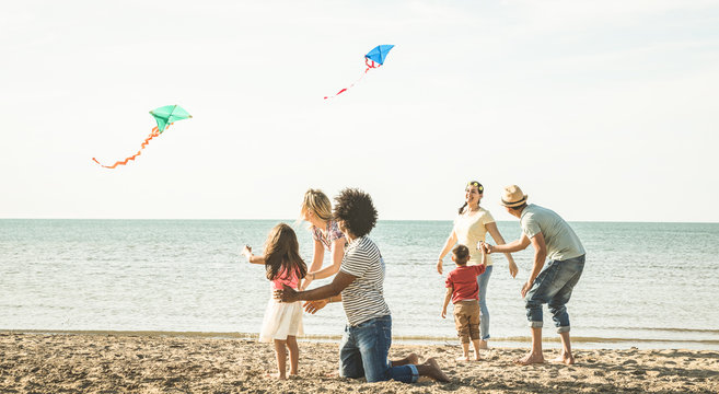 Group of happy families with parent and children playing with kite at beach vacation - Summer joy carefree concept with mixed race people having fun together at sunset  - Bright vintage  filter