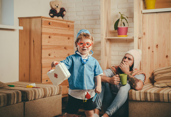 Hospital game, smiling boy dressed as doctor in red glasses holding first aid kit. Cute child with stethoscope playing with bearded dad, childhood concept. Patient with flu coughing in corner of room