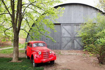 Poster Vintage voitures Red retro small vintage car standing in the garden in the summer on a background of gray hangar