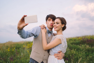 Romantic and happy caucasian couple in stylish clothes taking selfie  on the background of beautiful nature. Love, relationships, dating, romance, happiness concept. Man and woman having fun together.