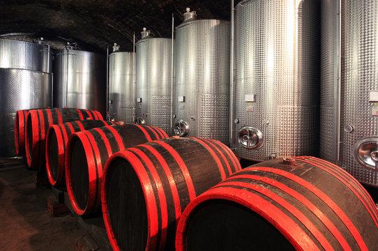 Wine barrels in wine cellar with modern fermentor tanks